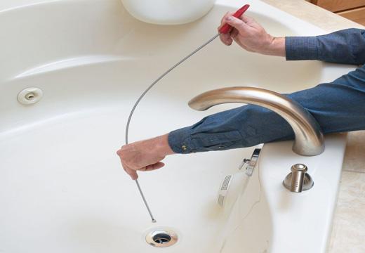 сантехник чистит тросом ванную