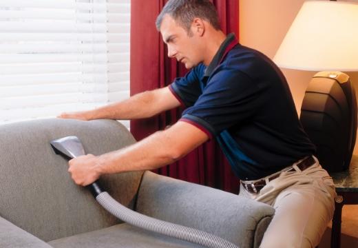 мужчина чистит диван
