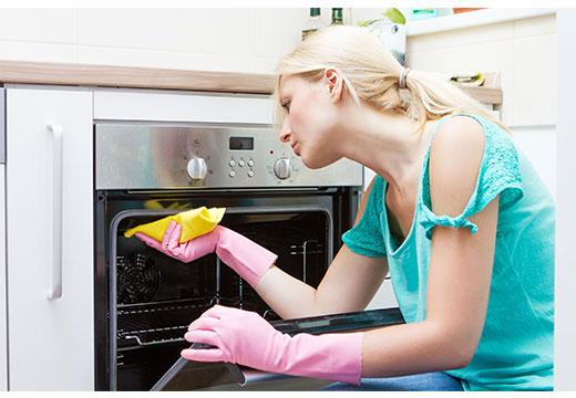 Девушка моет духовку